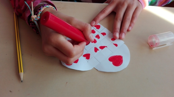 verflochtenes Herzenswunsch-Herz aus Papier mit aufgemalten Herzen