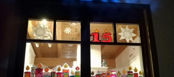 Außenfotografie eines beleuchteten Fenster, ausgeschmückt mit halbtransparenten bunten KerzenbildernKerzen