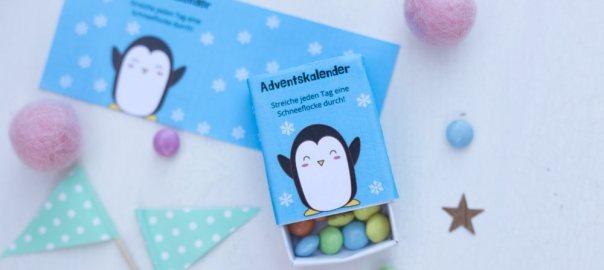 im Vordergrund: Eine Streichholzschachtel mit Pinguinbild und der Aufschrift Adventskalender - Streiche jeden Tag eine Schneeflocke durch! In der Schachtel sind Smarties. im Hintergrund: Fähnchendeko, Sternchen
