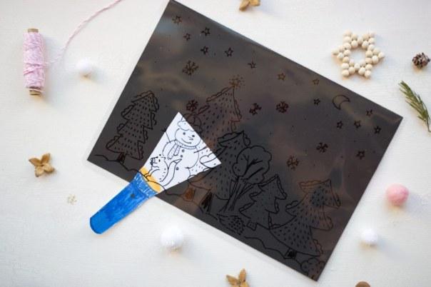 Eine durchsichtige Folie mit schwarzen Zeichnungen, auf schwarzem Papier als Untergrund. Eine Papier-Taschenlampe ist dazwischengesteckt, damit Bereiche des Bildes ausgeleuchtet werden können, indem der Hintergrund nicht mehr die gleiche Farbe wie die Zeichnungen hat.