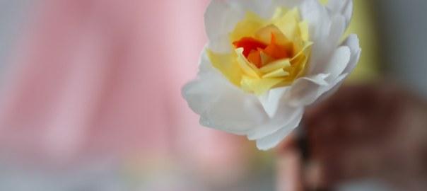 Eine Papierblume, vor verwischtem Hintergrund
