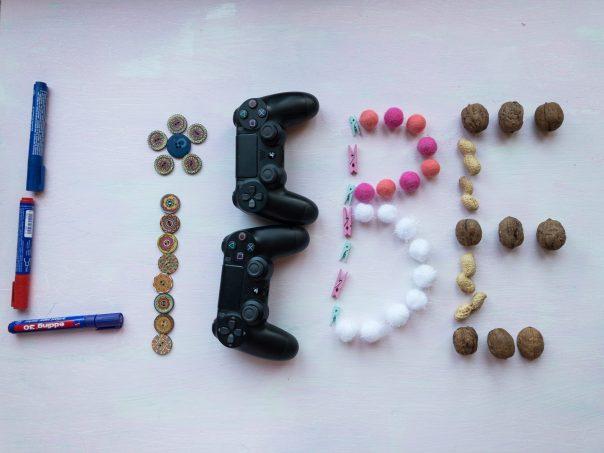 Das Wort LIEBE, buchstabiert mit verschiedenen Gegenständen: Das L wurde mit Textmarkern gelegt, das I mit Knöpfen, das E mit Videospielcontrollern, das B mit kleinen Klammern und bunten Papierbällchen, das E mit Nüssen
