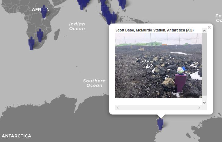 Zoom auf die Weltkarte, mit Fokus auf die Antarktis. Eine Carl-Markierung verweist mit einer Blase auf ein Bild mit einem Papier-Carl mit Schal und Mütze, im Hintergrund sieht man Scott Base