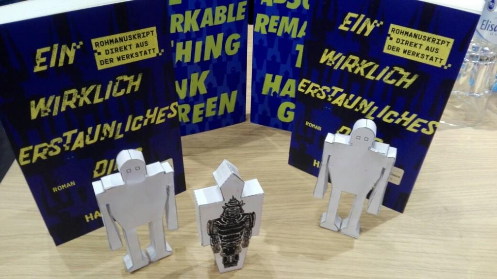 2 Exemplare der englischen Ausgabe An Absolutely Remarkable Thing und 2 Exemplare der deutschen Ausgabe Ein wirklich erstaunliches Ding, von Hank Green, davor stehen 3 Papier-Carls, 2 davon in der deutschen Roboter-Form und einer in der englischen, stilisierten Form.