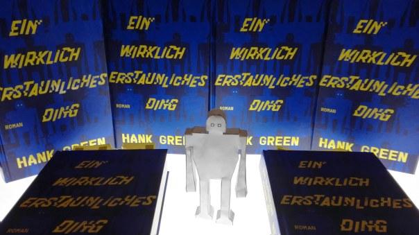 6 Exemplare des Buchs Ein wirklich erstaunliches Ding, von Hank Green, auf einem Leuchttisch, zwischen ihnen steht eine Papierfigur in Form eines Roboters